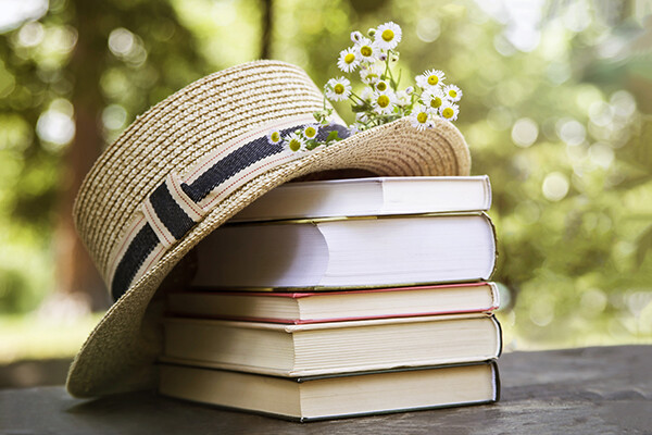 stack of books on an outdoor table topped with a straw hat and wild feverfew flowers