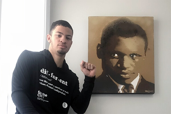 Jelani Williams holds up a fist of solidarity while seated next to a painting of singer, actor, athlete, and political activist Paul Robeson.