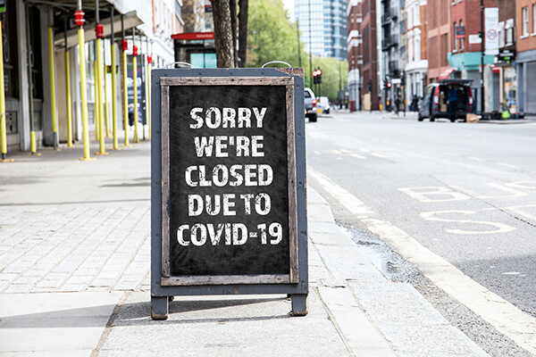 "Sandwich board on a city sidewalk that reads ""Sorry we're closed due to COVID-19"""