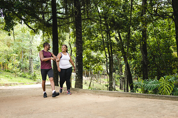 Two people in athletic gear walking on tree-lined path