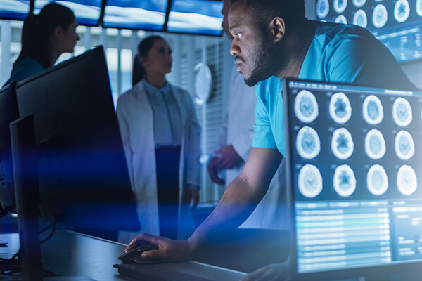 One person stands before two computer monitors while two people stand behind them, all in lab garments or white coats, one computer has brain scans on the screen