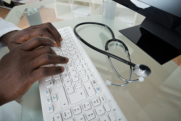 doctor typing on computer keyboard with stethoscope on desk
