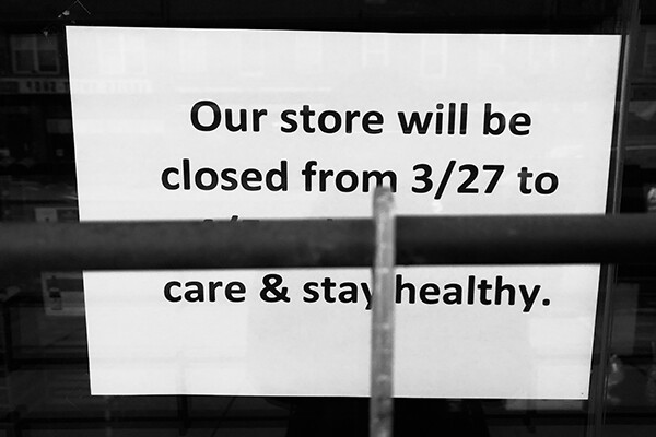 Posted sign partially obscured by window bars that reads: Our store will be closed from 3/27 to…care and stay healthy.