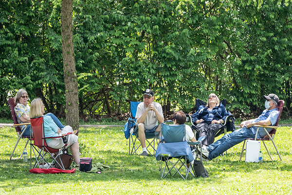 Six people sit socially distanced in folding camping chairs in a public park