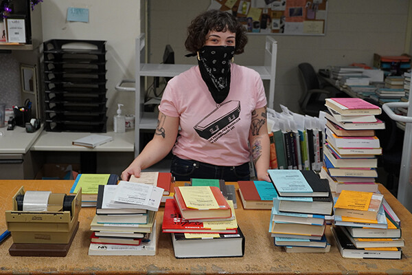 A person wearing a face covering stands in front of a table of books prepared for pickup.