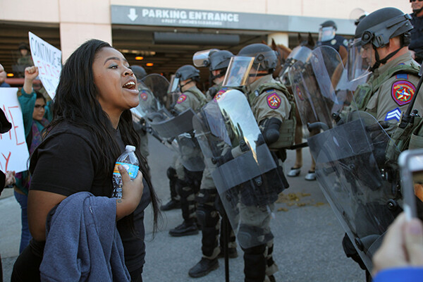 African American person in a crowd at a demonstration confronts a line of state police with riot gear.