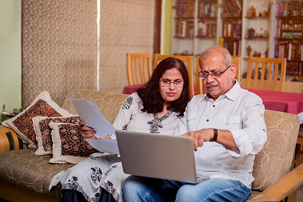 Older couple sitting on a couch looking at a laptop, one partner holds papers in their hand.