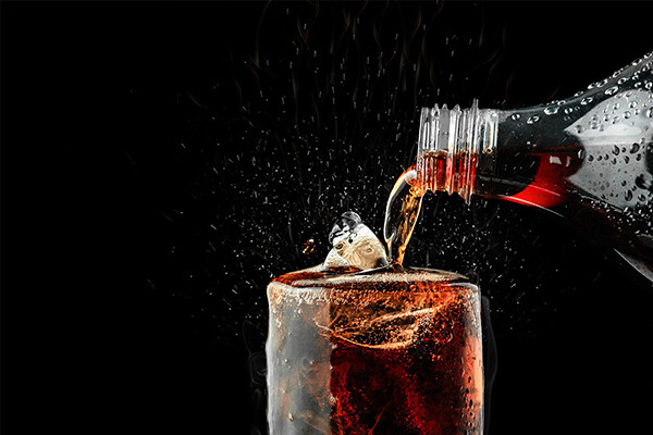Closeup of a bottle of cola being poured into a glass with ice.
