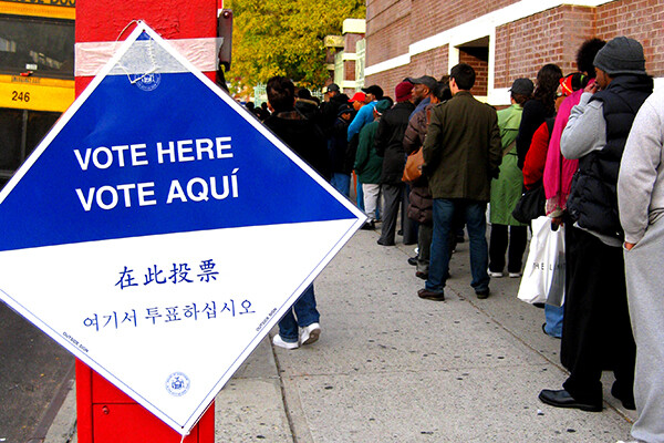 line of people at a polling place with a sign out front reading VOTE HERE/VOTE AQUI and also in Mandarin and Cantonese.
