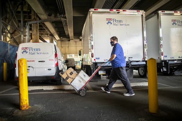 Man pushes hand cart carrying mail to be sorted with Penn Mail Services trucks in background.