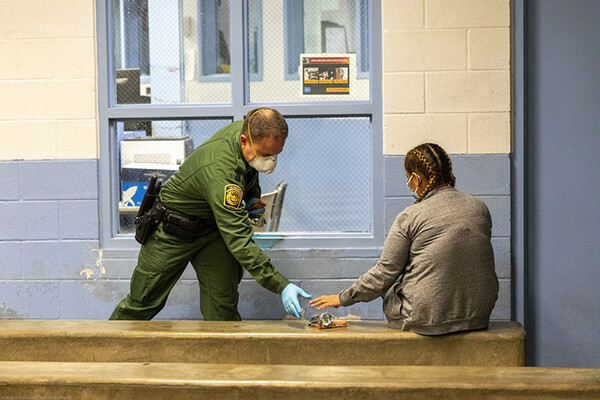 Uniformed border patrol personnel at a border processing center in a face mask and latex gloves hands an item to a detained person sitting on a bench.