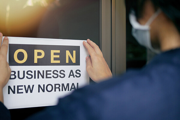 "Masked person puts a sign on door that says ""OPEN BUSINESS AS NEW NORMAL"""
