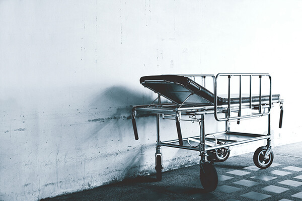 Single hospital bed in an abandoned hallway