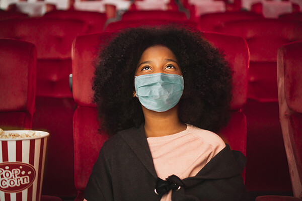 Young woman wearing mask in movie theater