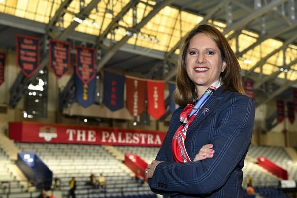 Standing in the Palestra on the floor, AD Grace Calhoun poses with her arms folded.