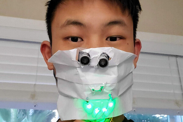 Face of high school student wrapped in a paper face covering mask with sensors attached that are glowing green.