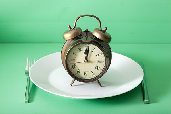 Old-fashioned alarm clock on top of an empty plate with a table setting