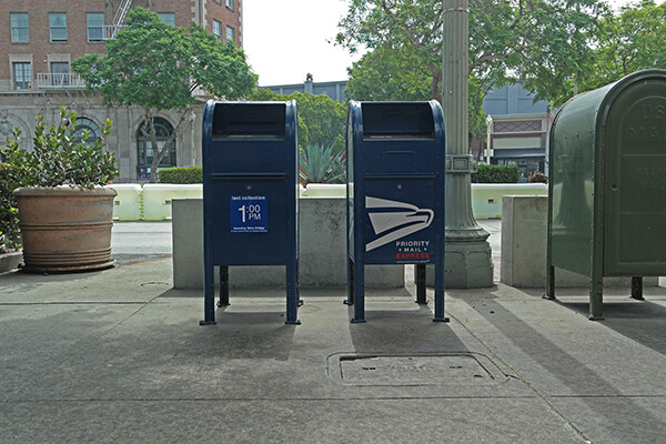Two U.S. postal service mail boxes sit side by side on a sidewalk with trees behind them and a the first few floors of a red brick building on the left in the background