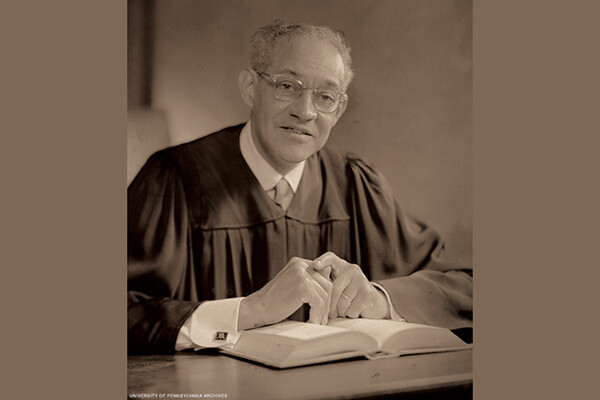 Historical photo of Raymond Pace Alexander wearing a judge robes seated at a table over an open book.