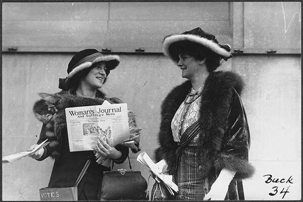 Two women in 1920 standing in fur lined coats and fancy hats, one holds a newspaper called Woman's Journal and Suffrage News.