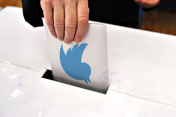 Hand stuffing a paper in a ballot box with the blue Twitter logo visible on the paper.
