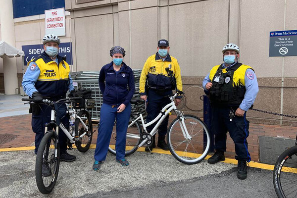 Penn DPS police officers wearing face-coverings standing with bikes in front building on campus