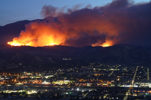A wildfire rages in the mountains above a city in California.