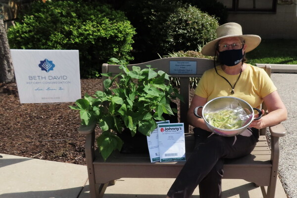 Person with a mask sitting on a bench holding a bowl of green beans next to a sign that says Beth David