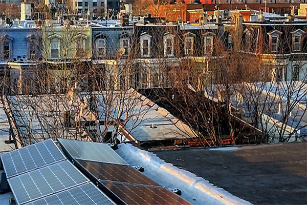 Philadelphia rowhouse roofs with solar panels in foreground and city skyline in background.