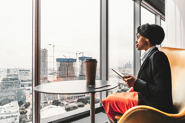 Professional African American person using a digital tablet looking out the windows on the top floor of a city office skyscraper.