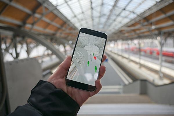 hand holding a smartphone in a public transit station tracking human images on the screen in red or green indicating covid exposure