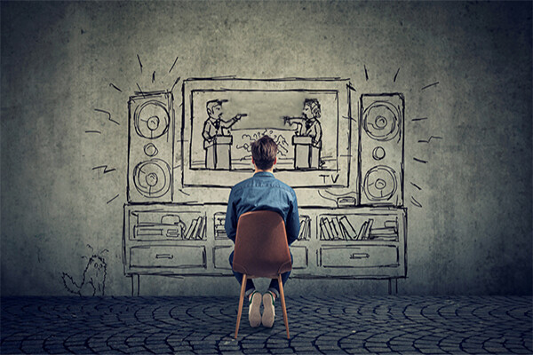 person sits in chair facing wall with drawing of two people debating on a television