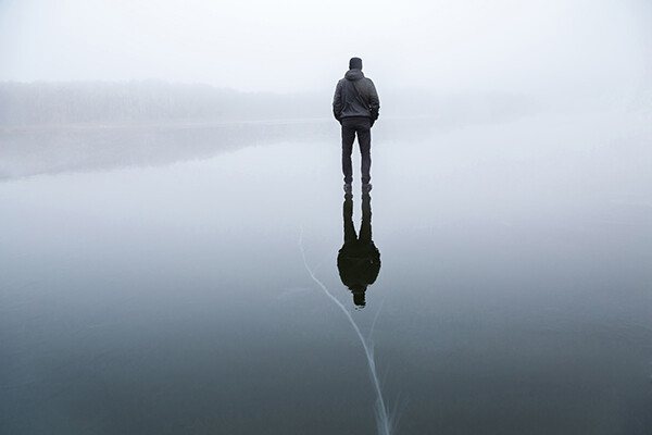 Person standing on frozen lake with back turned on a grey day.