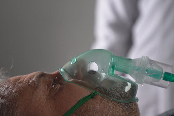 Person lying on back in hospital bed receiving oxygen via a mask.
