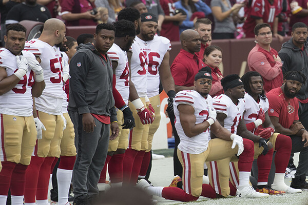 Members of the 49ers football team kneeling on the field before a game.