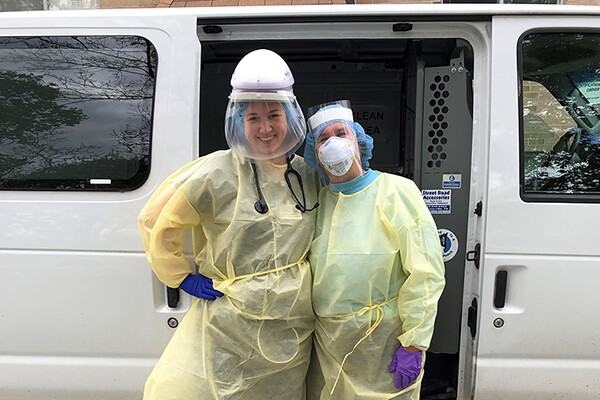Two medical workers in full PPE standing outside a medical transit van.