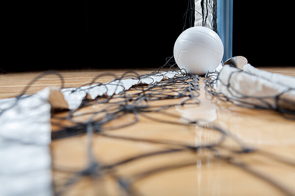 Volleyball on the ground on top of a collapsed net on a gym floor.