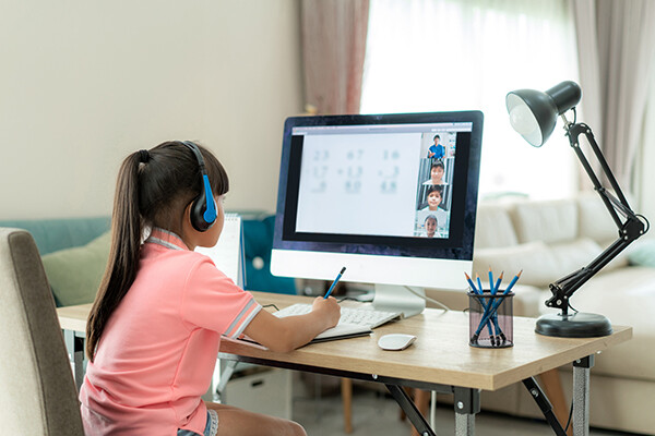 Young elementary school student at a home computer attending virtual school.