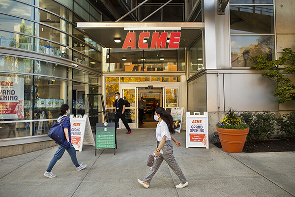 people walk past the new ACME market