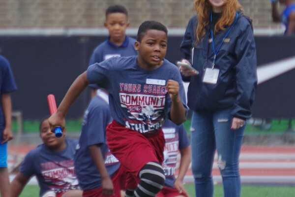 At Franklin Field, a student from West Philadelphia runs with a baton during a track & field practice.