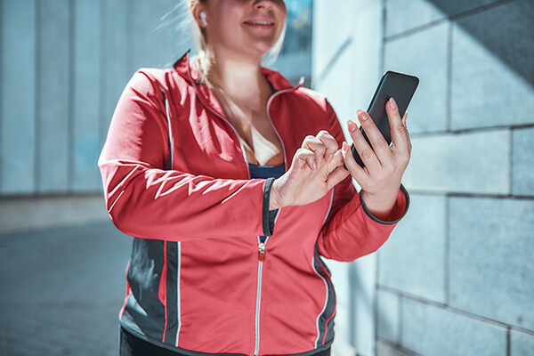 person in exercise gear looking at their phone with earbuds in.