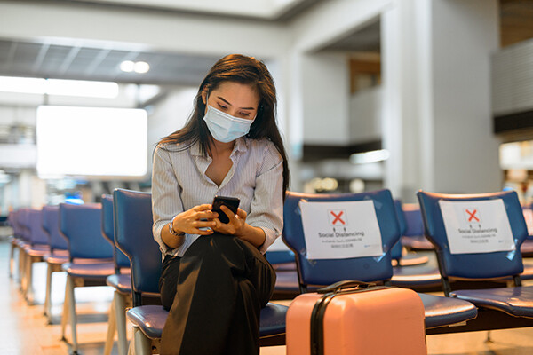 "Person sitting cross-legged on an airport chair looking at a phone. A suitcase is in front of the image. A chair next to the person has a large, red X and read ""Social Distancing."""