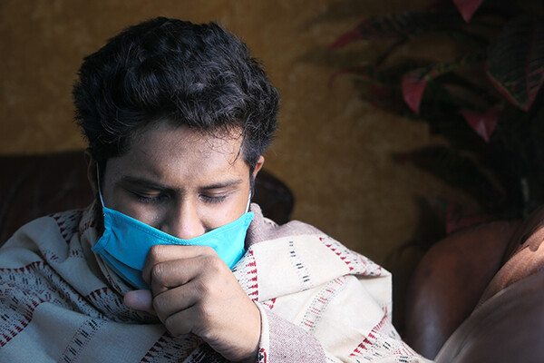 Person wearing face mask and wearing a blanket coughing into fist.