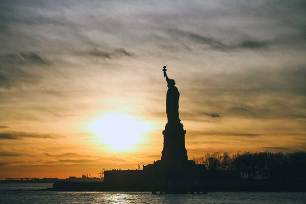 Statue of Liberty in shadow in New York Harbor as the sun sets behind