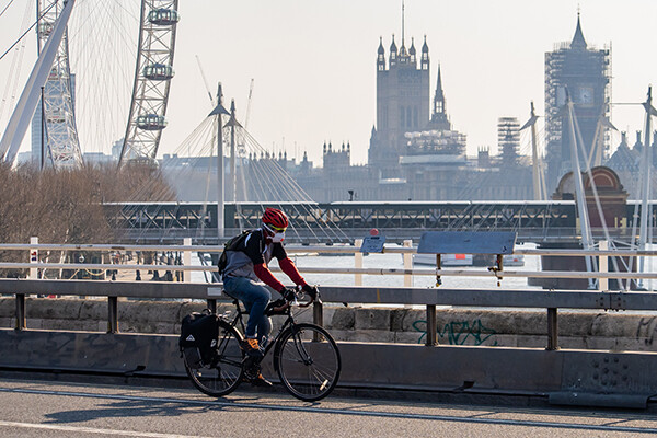 Person wearing a face mask riding a bike with the London cityscape in the background.
