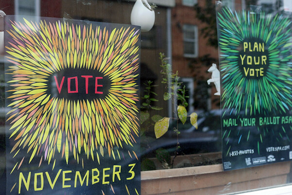 Two handmade signs in a window that read VOTE NOVEMBER 3 and PLAN YOUR VOTE.