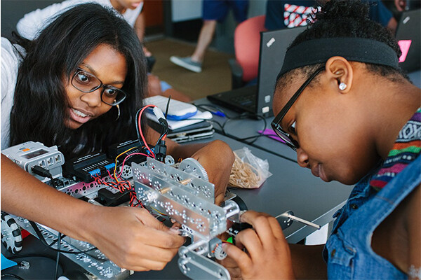 two middle school-age students work on a robotics project.