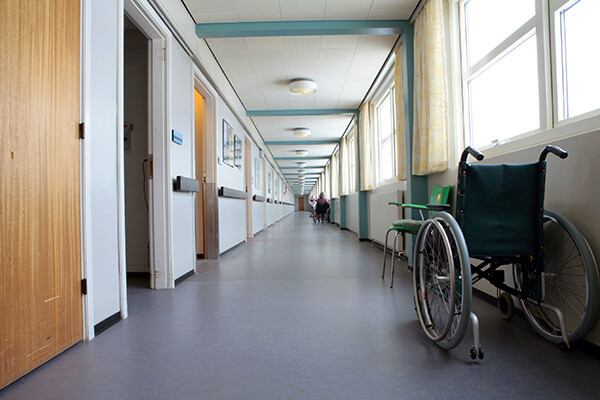 Nursing home hallway with an empty wheelchair parked outside an open door.