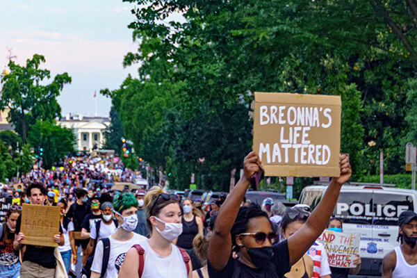 Large crowd wearing masks protesting in the streets of D.C., person in foreground holds a sign reading BREONNA'S LIFE MATTERED.