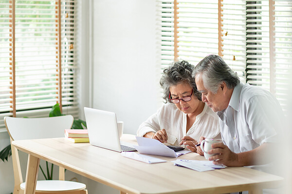 Aging couple looking at financial papers and a laptop with concern at a kitchen table.